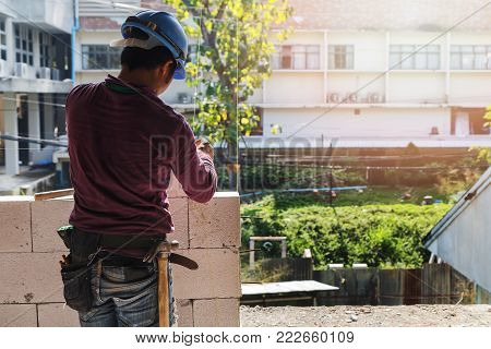 Bricklayer Plastering Cement On Brick. Mason Worker Building Exterior Walls.