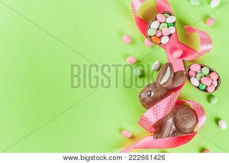 Easter holiday greeting card background, with chocolate easter bunny, candy eggs, quail eggs and festive ribbon, copy space top view