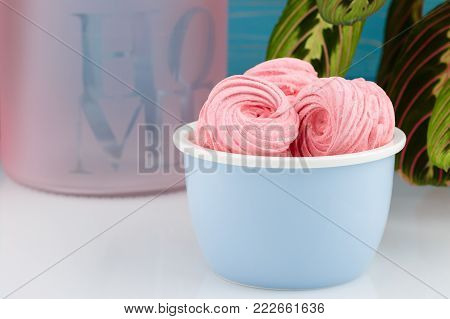 Homemade pink zephyr or marshmallow in blue bowl on table with plant. Marshmallow, Meringue, Zephyr