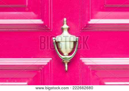 Knocker. Old antique golden knocker on the abstract pink wooden doors for knocking close up