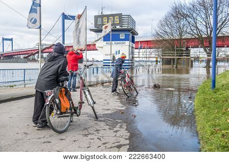 DUISBURG GERMANY - JANUARY 08 2017 : Bike drivers surprised by the river Rhine flooding the promenade in Ruhrort