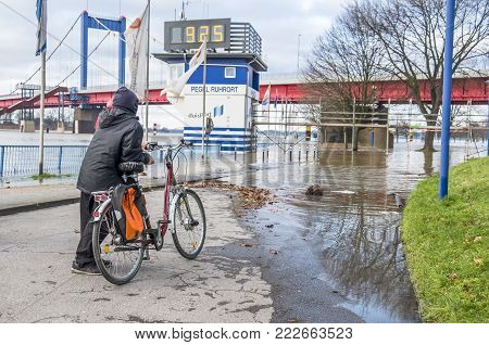 DUISBURG GERMANY - JANUARY 08 2017 : Bike driver surprised by the river Rhine flooding the promenade in Ruhrort