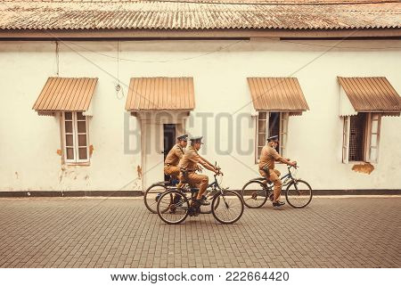 Galle, Sri Lanka - Dec 23, 2017: Group Of Policemen In Retro Uniform Riding Bicycles In Historical C