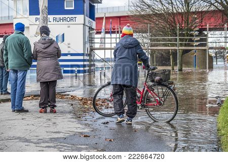 DUISBURG , GERMANY - JANUARY 08 2017 : Lady surprised by the river Rhine flooding the promenade in Duisburg - Ruhrort