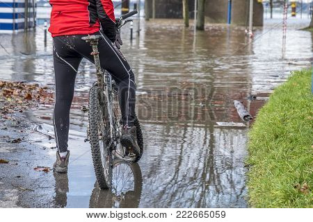 DUISBURG , GERMANY - JANUARY 08 2017 : Bike driver surprised by the river Rhine flooding the promenade in Ruhrort