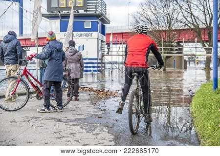 DUISBURG , GERMANY - JANUARY 08 2017 : Bike drivers surprised by the river Rhine flooding the promenade in Ruhrort