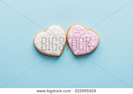 top view of two glazed heart shaped cookies isolated on blue, st valentines day holiday concept