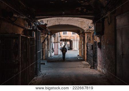 Man walking alone through old passage in Odessa,Ukraine.