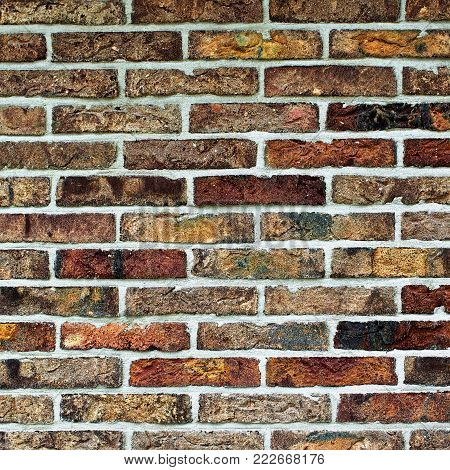 Background of Multi Colored Old Brick Wall with Cracked Surface and Concrete closeup Outdoors