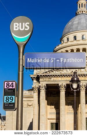 Paris, France - July 03, 2017: Pantheon bus stop sign with the Pantheon in the background in the summer at sunset.The Pantheon is a secular mausoleum containing the remains of distinguished French citizens.