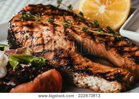 deep fried fish slice laying plate with orange slice