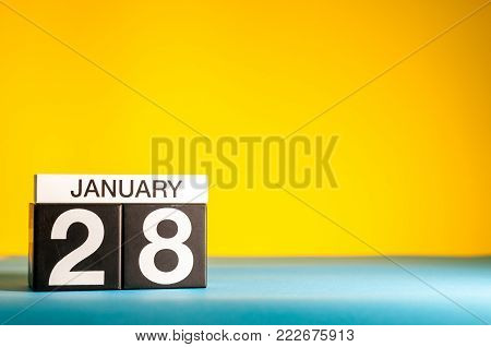 January 28th. Day 28 of january month, calendar on yellow background. Winter time. Empty space for text.