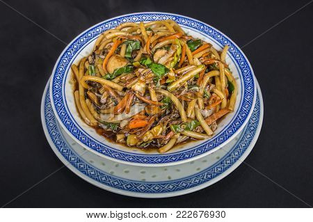 Chinese food. Stir fry noodles with mushrooms, Chinese cabbage and carrot on the porcelain plate. Close up. Black background.