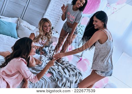Top view four playful young smiling women in pajamas bonding together while having a slumber party