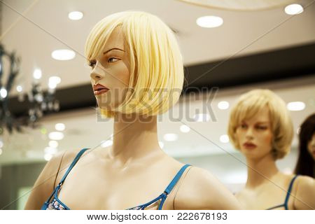 Two glamour blonde mannequins in a shopping mall. Cruel bitchy woman hatching up revenge behind friend's back