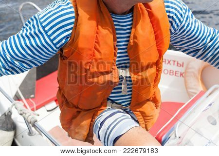 The orange life jacket is put on a body of the person in hay - a white t-shirt to a stripped vest outside in the summer