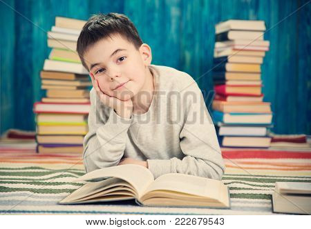 eight years old child reading a book at home. Boy studying at table on blue background