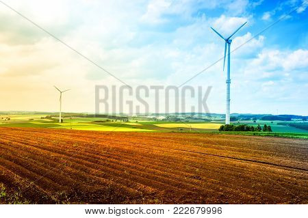 Country landscape with wind turbines and agricultural fields. Nature background