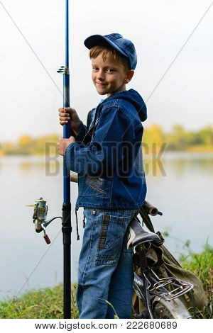 A Fisherman Boy On The River Bank With A Fishing Rod In His Hands. He Wants To Catch A Big Fish..