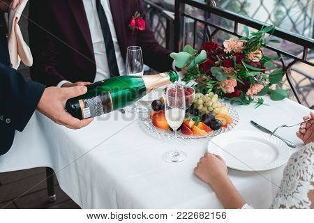 Weddings toast. glasses with champagne drink in bride and groom hands, gold wedding ring in focus. Happy newlyweds drinking at ceremony. Loving couple created new family. Decorated alcohol drinks