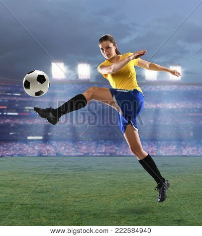 Young female soccer player kicking ball inside large stadium