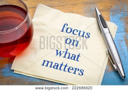 Focus on what matters reminder - handwriting on a napkin with a cup of tea