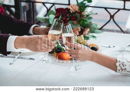 Weddings toast. glasses with champagne drink in bride and groom hands. Happy newlyweds drinking at ceremony. Loving couple created new family. Decorated alcohol drinks