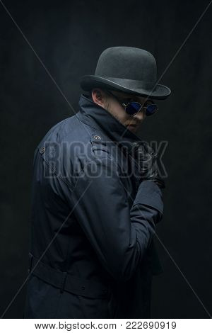 Robber in a hat, glasses and black gloves