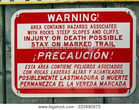 A warning sign in an area of very steep slopes and rocky cliffs showing hazards for people to take precautions in english and spanish