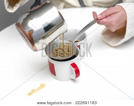 Woman spilling coffee on the table while pouring in cup, indoor closeup