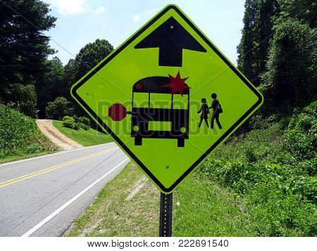 A warning sign indicating the imminent school bus stop and beware of children crossing