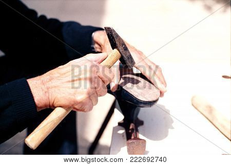 An old artisan shoemaker is fixing a shoe with a hammer.