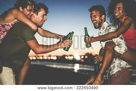 Happy friends drinking beer and having fun on the beach after sunset - Young people enjoying summer vacation - Youth ,holidays, party and friendship concept - Soft focus on right man face