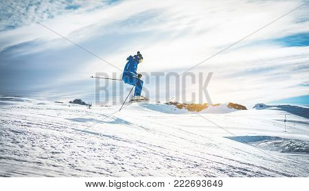 Ski athlete performing acrobatic jump on downhill at sunset - Adult skier riding down for winter time in ski slope - Extreme snow sport and holidays concept - Focus on him - Soft vignette editing