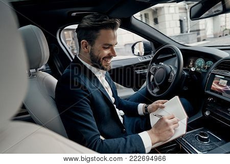 And then I am going to meet with...  Handsome young man in full suit writing something down in personal organizer and smiling while sitting inside of the car