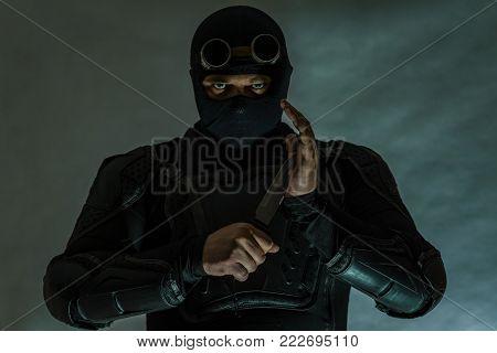 Secret agent in bulletproof vest. Balaclava. A military knife is prepared for a strike. Dark.