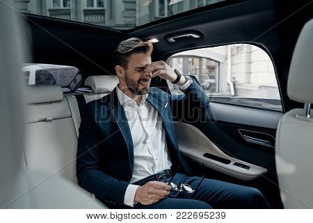 Having a headache. Frustrated young man in formalwear massaging nose and keeping eyes closed while sitting in the car
