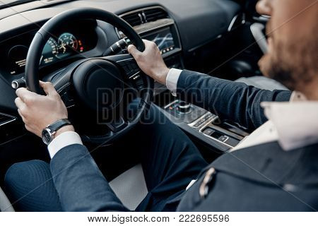Busy working day. Close up top view of young man in formalwear keeping hands on the steering wheel while driving a luxury car