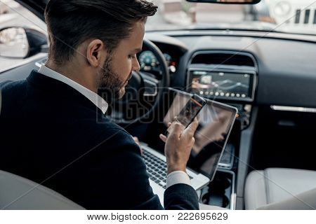 Always in touch. Top rear view of young man in formalwear using his smart phone while sitting in the car