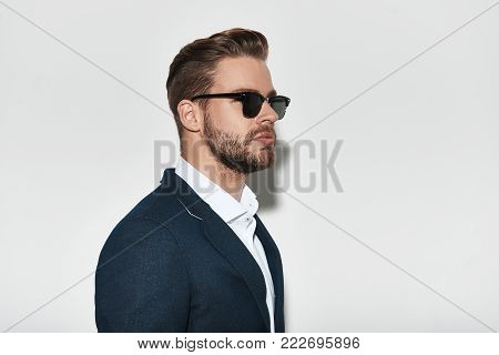 Portrait of elegance. Handsome young man in formalwear looking away while standing against grey background