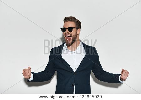 Success achieved! Handsome young man in formalwear gesturing and smiling while standing against grey background