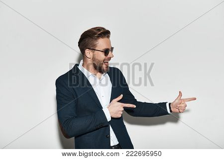 Look at that! Handsome young man in formalwear pointing copy space and smiling while standing against grey background