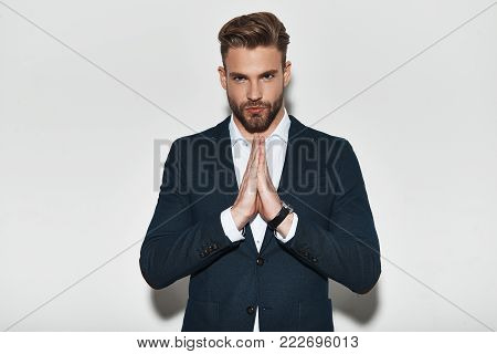 Confidence and charisma. Handsome young man in formalwear holding hands clasped and looking at camera while standing against grey background