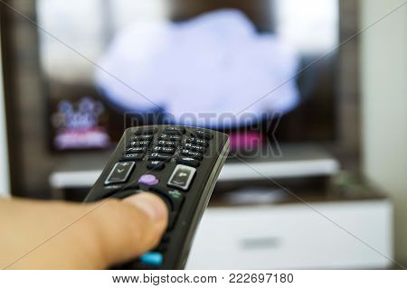 watching TV and changing the channels with the control, changing the TV channels with the control