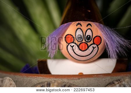 Portrait of a figurine of a clown with a smiling face stuck in a flower pot