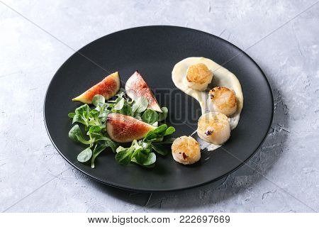 Fried scallops with lemon, figs, sauce and green salad served on black plate over gray texture background. Plating, fine dining