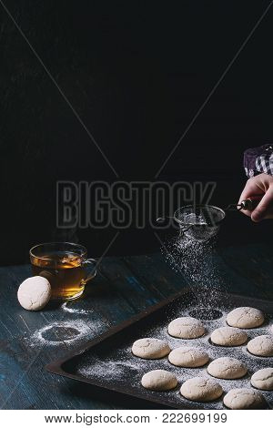 Homemade almond cookies on old oven tray and cup of hot tea over dark blue wooden table. Sprinkling sugar powder by vintage sieve in child hand. Dark rustic style. Top view, space