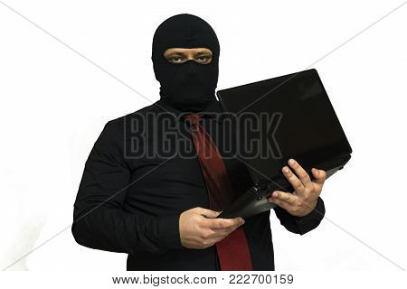 Electronic burglar in the balaclava. In the hands of a laptop. Looks at you. computer crime