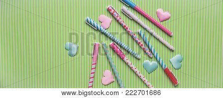Pastel flat lay with girlish pens and hearts on striped green background