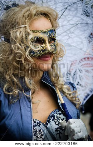 Venice, Italy - February 26th, 2011: Elegant lady with a white umbrella, on the face mask and traditional clothing Venetians During the Carnival in Piazza San Marco